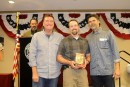 Nate Ferris receives the Under 50 Gold Glove from coaches Eric Rasmussen and Rick Aguilera.